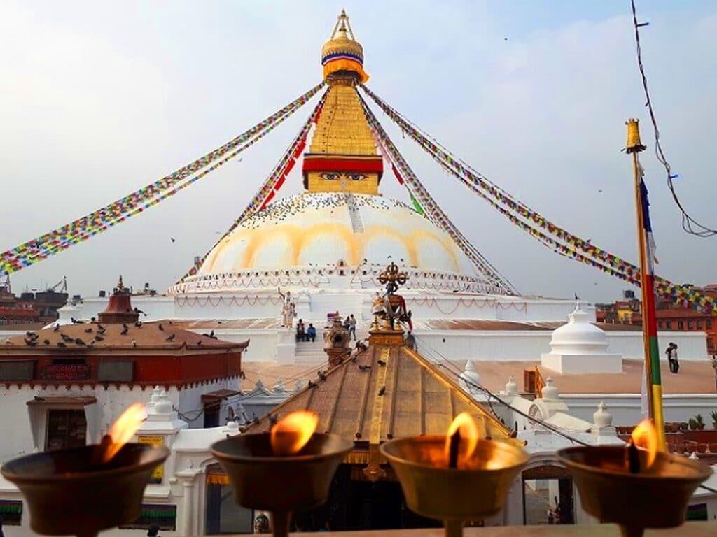 Boudhanath Stupa mit brennenden Kerzen und Gebetsfahnen in Kathmandu Nepal