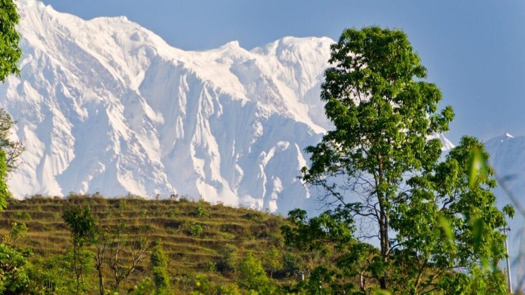 Annapurna Kette zu sehen mit grünen Hügeln davor