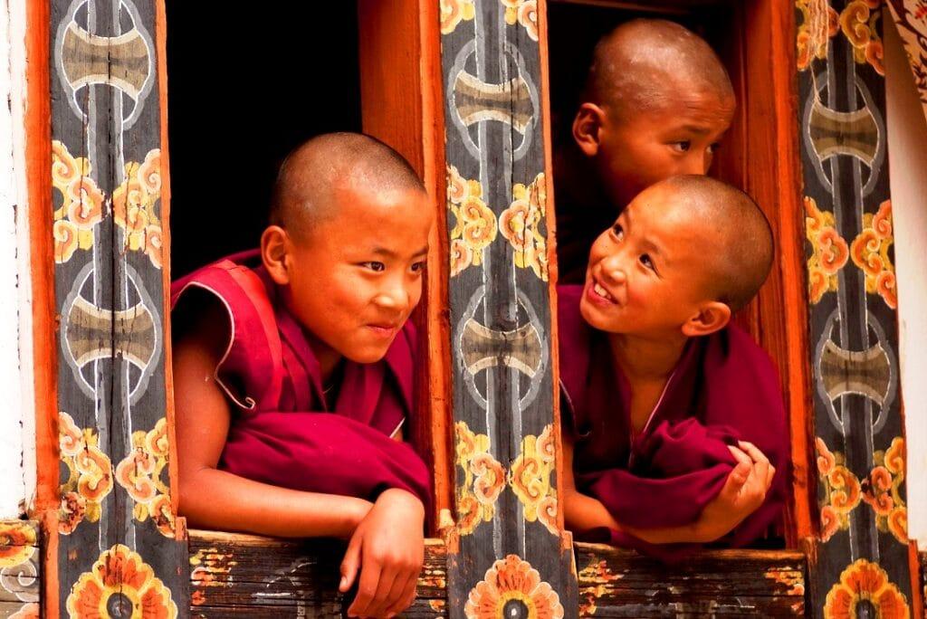 Kindermönche in Bhutan schauen aus dem Fenster