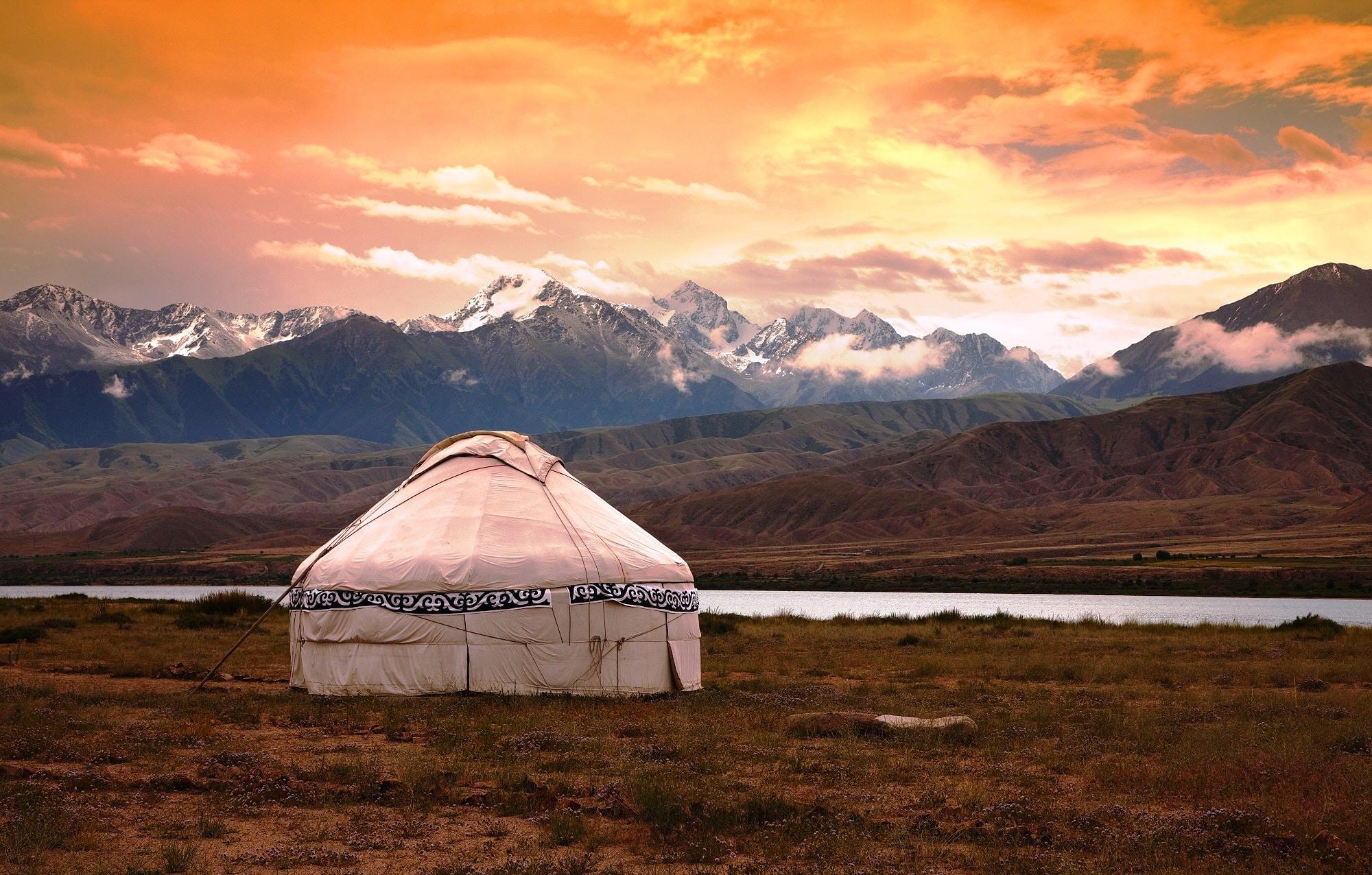 Nomaden Jurten in Kirgistan mit Gebirgssee und Berge im Hintergrund